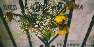 flowers on fence outside headstone