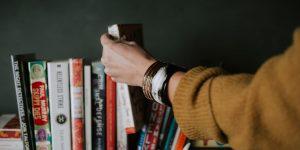 arm choosing a book from shelf